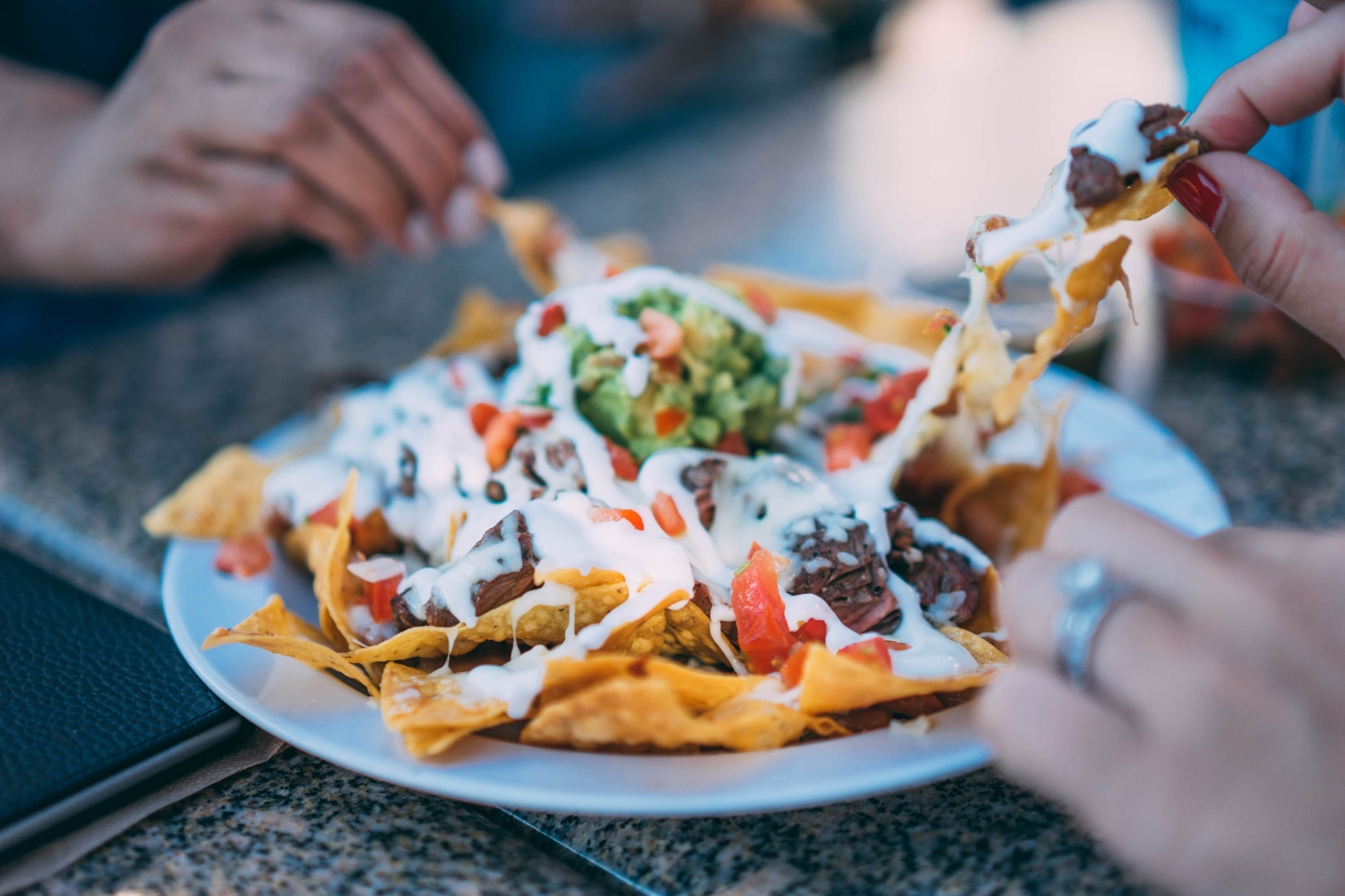 Nachos and Cheese being grabbed by many hands